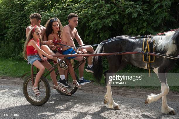 People travel on the back of a horsedrawn carriage along Long Marton Road on the opening day of the annual Appleby Horse Fair in the town of...