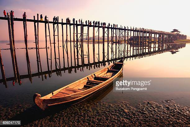 People traveling across the U Bein Bridge in the evening. Mandalay Myanmar with sunset