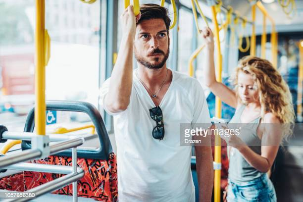 people traveling by public bus - commuters in the city bus - mid adult men stock pictures, royalty-free photos & images