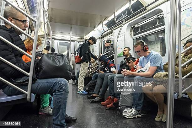 people traveling in a subway train in new york city - crowded subway stock photos and pictures