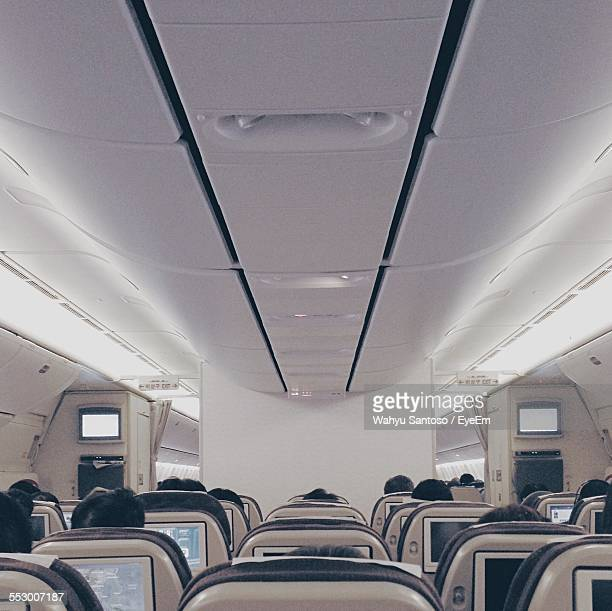 people traveling in airplane - vehicle interior stock pictures, royalty-free photos & images