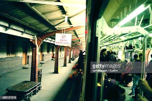 people traveling in train by empty railway station platform - train interior stock photos and pictures