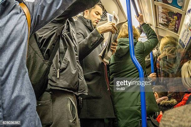 people travelling on crowded london underground train - affollato foto e immagini stock