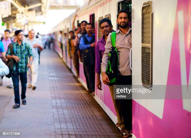 people travelling on local indian train into mumbai - mumbai stock pictures, royalty-free photos & images