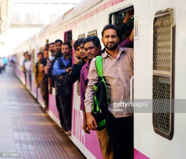 People travelling on local Indian train into Mumbai