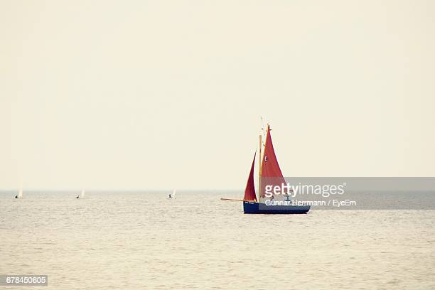 People Travelling On Sailboat At Sea Against Clear Sky