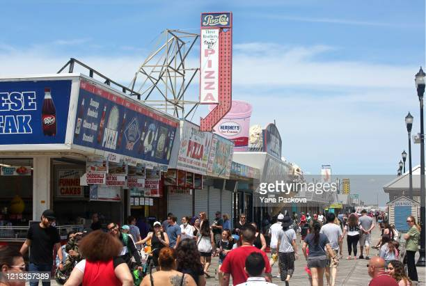 People traverse the Seaside Heights boardwalk as the state begins to reopen beaches and boardwalks amid the novel coronavirus pandemic on May 16,...