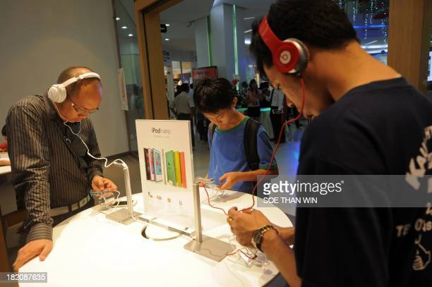 People try Apple products at a shop at a shop on its opening day at a mall in Yangon on September 28 2013 Apples first authorized reseller in Myanmar...