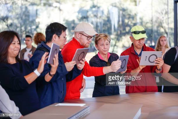 People try out the augmented reality system that shows what the finished Apple Park will look like at the opening of the Apple Park Visitor Center on...