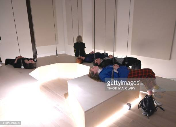 """People try out the display """" Daily tous les jours, I Heard There Was a Secret Chord, 2017"""" a participatory audio installation in an octagonal..."""