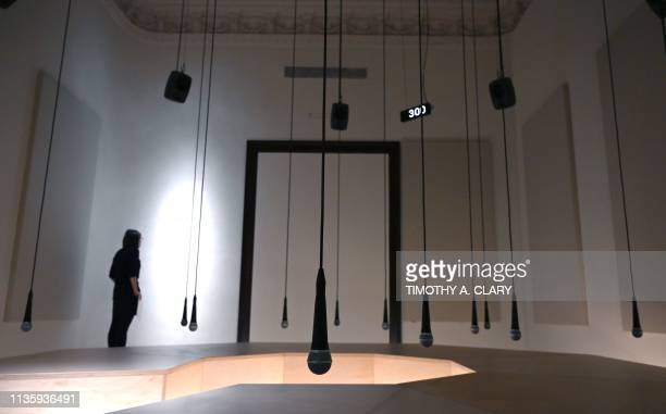 People try out the display Daily tous les jours I Heard There Was a Secret Chord 2017 a participatory audio installation in an octagonal...
