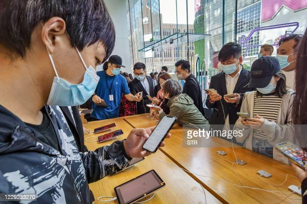People try out the new iPhone 12 mobile phones at an Apple store in Shanghai on October 23, 2020. / China OUT