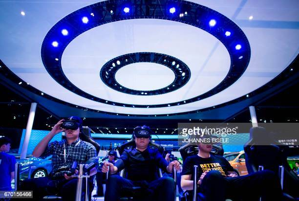 People try out virtual reality goggles at a stand for US carmaker Ford during the first day of the 17th Shanghai International Automobile Industry...