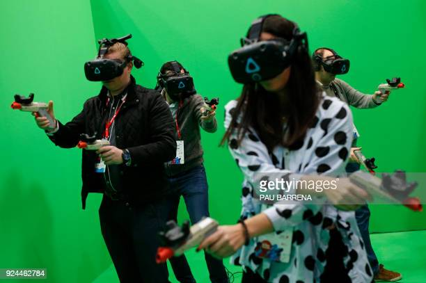 People try the HTC VIVE virtual reality glasses at the Mobile World Congress the world's biggest mobile fair on February 26 2018 in Barcelona the...
