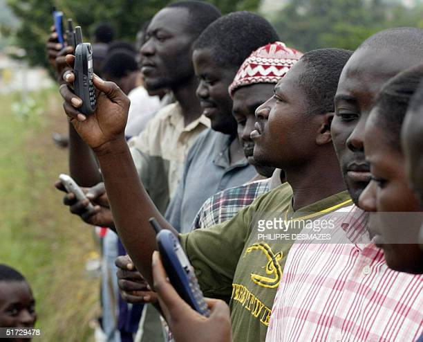 People try to call via their cell phones after a rumour that the network has been restored, 11 November 2004 in the rebel-held city of Bouake,...
