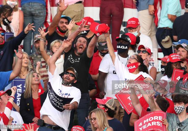 People try to catch a campaign hat being tossed into the crowd before the arrival of President Donald Trump during his 'The Great American Comeback...