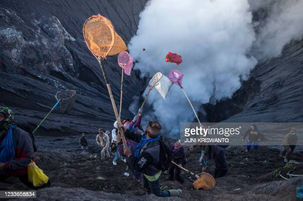 People try to catch offerings thrown by Tengger tribe people off the summit of the active Mount Bromo volcano in Probolinggo, East Java province on...