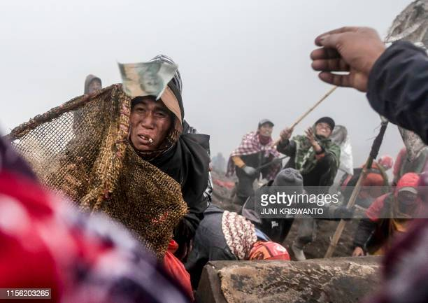 People try to catch offerings thrown off the summit of Mount Bromo volcano by Tengger tribe members and local tourists in Probolinggo East Java...