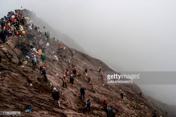 TOPSHOT People try to catch offerings thrown off the summit of Mount Bromo volcano by Tengger tribe members and local tourists in Probolinggo East...