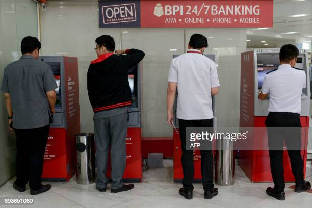 People try to check their balances on automated teller machines at a branch of the Bank of the Philippine Islands in Manila on June 8 2017 Bank of...