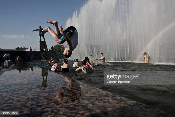 People try to cool off in a fountain. The temperature in the city is 33 degrees Celsius.