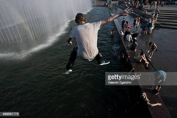 People try to cool off in a fountain. The temperature in the city is 30 degrees Celsius.