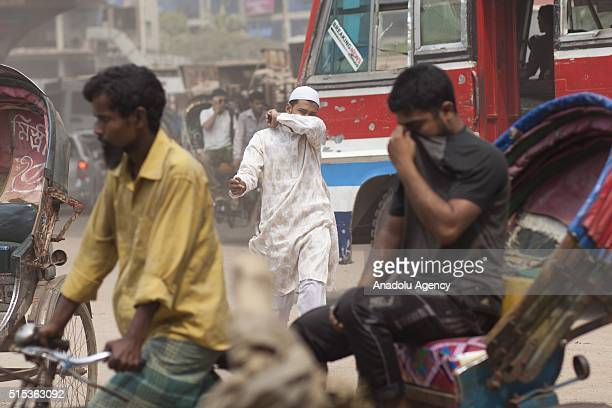 People try to cover their faces as dust blankets a busy street in Dhaka Bangladesh on March 13 2016 More than 55 million people worldwide are dying...