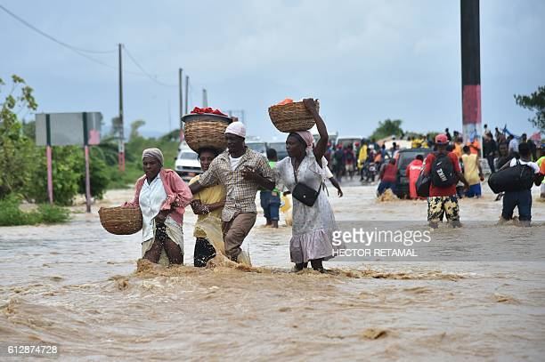 People try to cross the over flowing Rouyonne river in the commune of Leogane south of PortauPrince October 5 2016 Haiti and the eastern tip of Cuba...