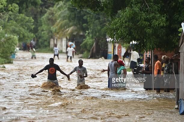 People try to cross the overflowing La Rouyonne river in the commune of Leogane south of PortauPrince October 5 2016 Haiti and the eastern tip of...