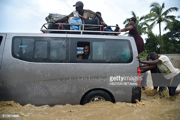 TOPSHOT People try to cross the overflowing La Rouyonne river in the commune of Leogane south of PortauPrince October 5 2016 Haiti and the eastern...