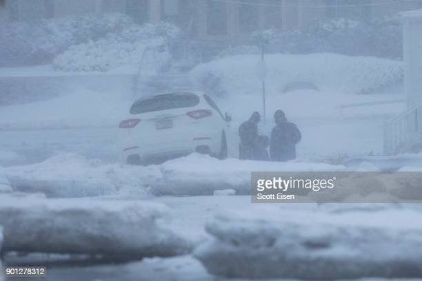 People try to free a Maserati SUV that got stuck on a chunk of ice as a massive winter storm bears down on the region on January 4 2018 in Scituate...