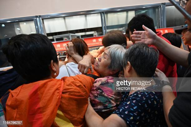 TOPSHOT People try to get a roast chicken at the first Costco outlet in China on the stores opening day in Shanghai on August 27 2019 China has...