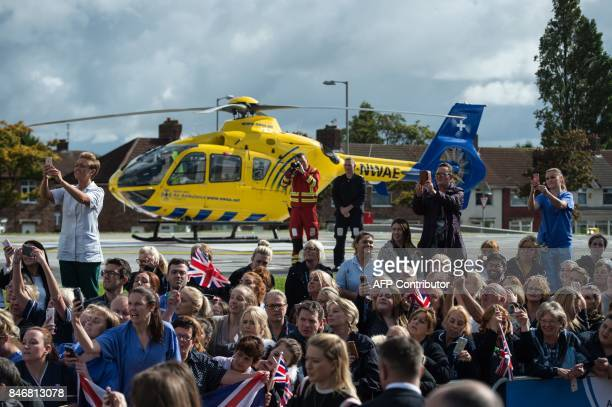 People try to get a view of Britain's Prince William Duke of Cambridge as he arrives to formally open the new Urgent Care and Trauma Centre at...