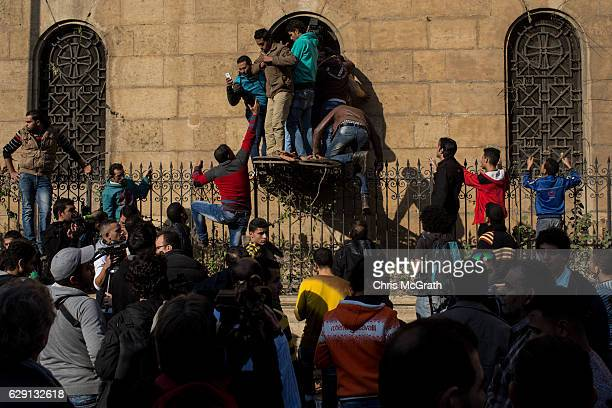 People try to look through a broken window into the destroyed interior of the church of St Peter and St Paul in the Coptic Cathedral complex on...