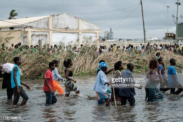 "People try to loot sacks of Chinese rice on which is written ""China Aid"" from a warehouse surrounded by water after the cyclone Idai hit the area, in..."