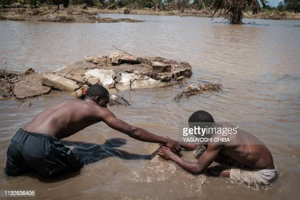 People try to recover house materials from water after a house was destroyed by the Cyclone Idai in John Segredo Mozambique on March 24 2019 Cyclone...