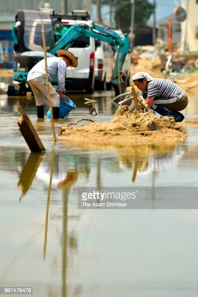 People try to remove floodwaters at Mabicho area on July 13 2018 in Kurashiki Okayama Japan The death toll from the torrential rain in western Japan...