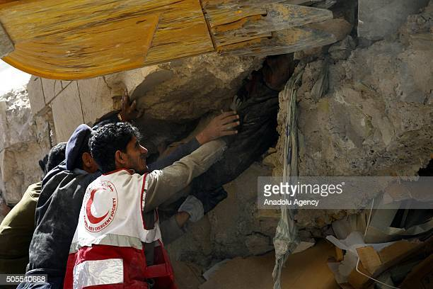 People try to rescue a person who was buried in the wreckage of Sana'a Police Headquarters after Saudiled coalition carried out airstrikes in the El...