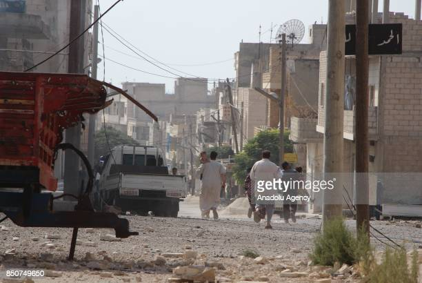 People try to run away near the wreckages after airstrikes hit Khan Sheikhun town of Idlib Syria on September 21 2017