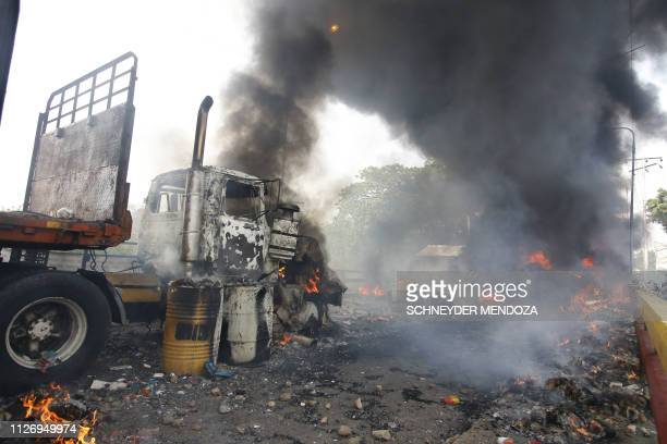 People try to salvage humaitarian aid after the truck carrying it was set ablaze on the Francisco de Paula Santander International Brige between...