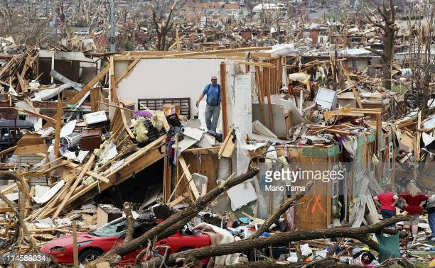 People try to salvage items from the Albrecht family home after it was destroyed when a massive tornado passed through the town killing at least 116...