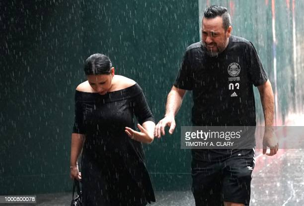 People try to take cover from the rain in Midtown New York on July 17 2018 as a sudden storm hit the area with flash food warning in the tristate area