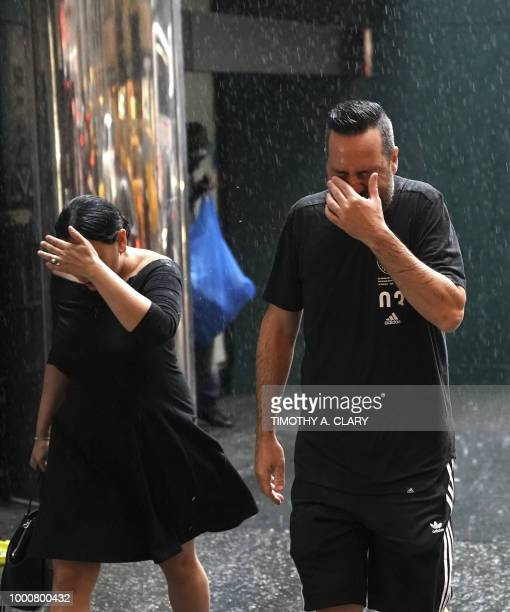 People try to take cover in Midtown New York on July 17 2018 as a sudden storm hit the area with flash food warning in the tristate area