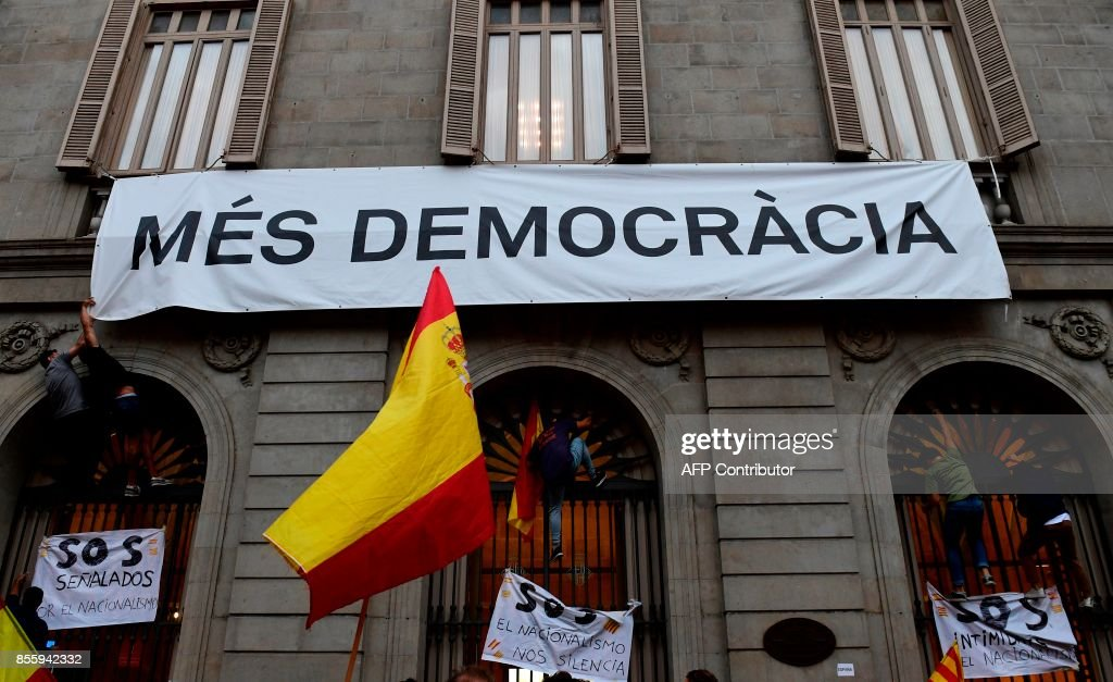 People try to take down a banner reading 'More democracy' during a demonstration against independence in Catalonia, on September 30, 2017 in Barcelona. Hundreds of people, many waving red and yellow Spanish flags, rallied in Barcelona in favour of Spanish unity today, a day before a banned independence referendum in Catalonia. /