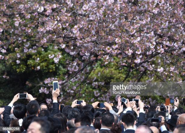 People try to take pictures of Japanese Prime Minister Shinzo Abe with their smart phones and cameras during the cherry blossom viewing party hosted...