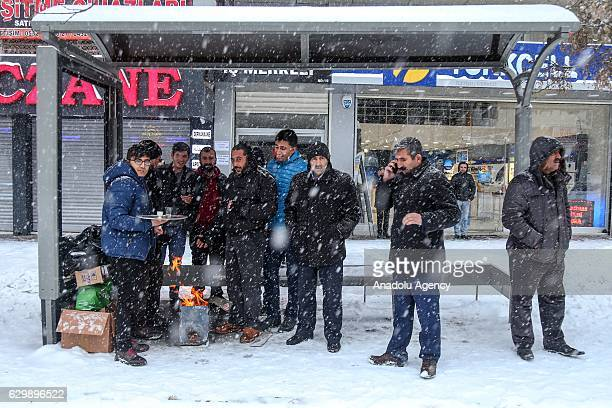People try to warm up at a bus station as heavy snowfall hits Van province of Turkey on December 15 2016