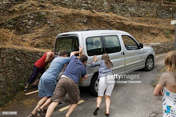 People trying to get a car up a hill