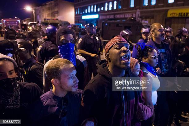 People trying to keep the peace stand in front of officers near the intersection of West North Avenue and Pennsylvania Avenue as protestors walk for...