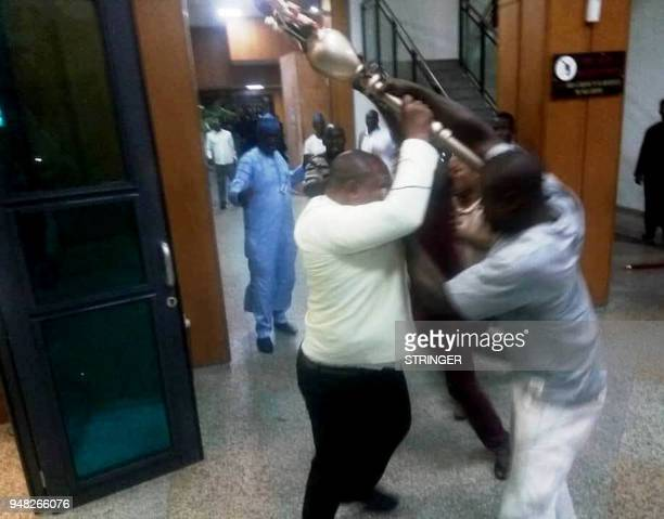 People trying to take possession of the mace the symbol of authority of the Upper Legislative Chamber seized at the chamber in Abuja on April 18 2018...