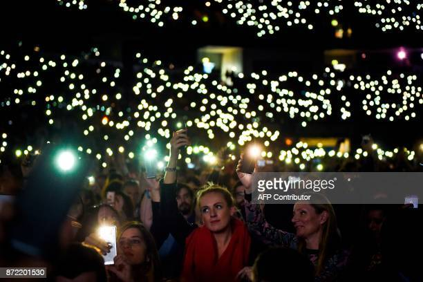 People turn on the flash lights of their mobile phones during the 2017 Web Summit in Lisbon on November 9 2017 Europe's largest tech event Web Summit...